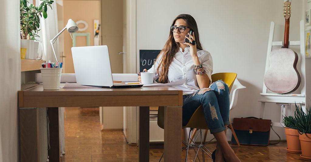 Mulher ao telefone, trabalhando em casa, exercendo o teletrabalho com conforto e organização