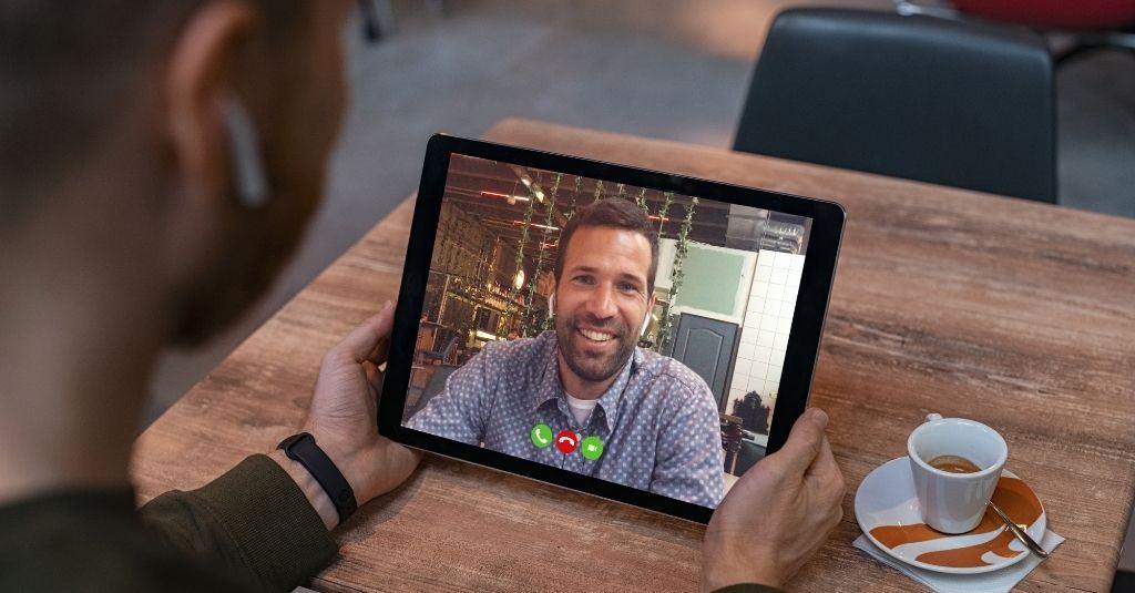 Homem sentado à mesa utilizando um tablet para fazer videochamada