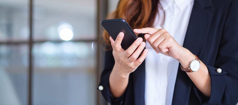 Mulher segurando o celular com close em suas mãos