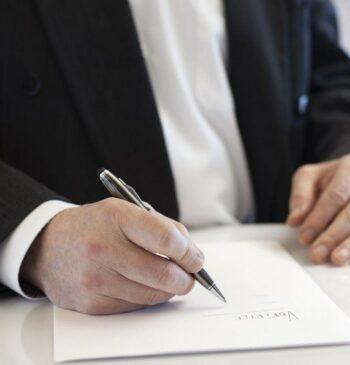 Mãos de homem segurando caneta para assinar um documento em papel