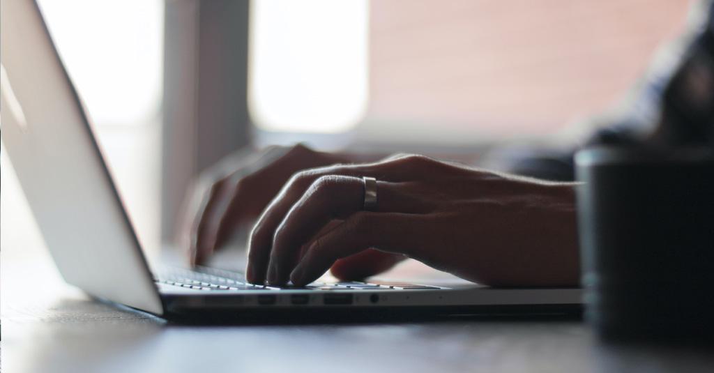 Pessoa digitando em notebook,. foco em suas mãos