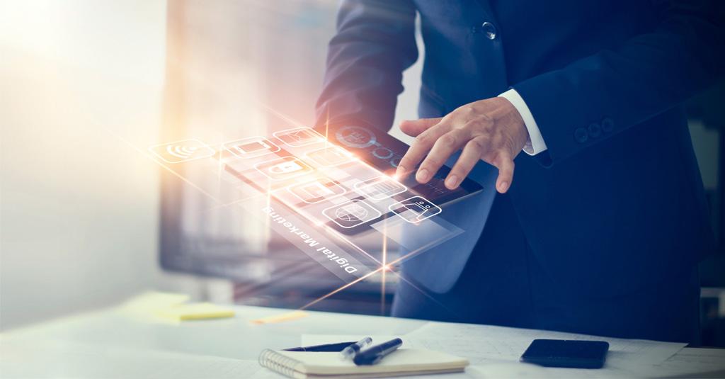Homem de terno em pé em frente a sua mesa, manuseando um tablet imaginário com todos os contratos em nuvem