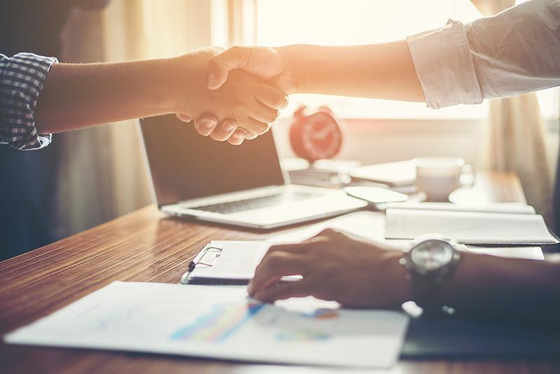 Duas pessoas apertando as mãos fechando um contrato