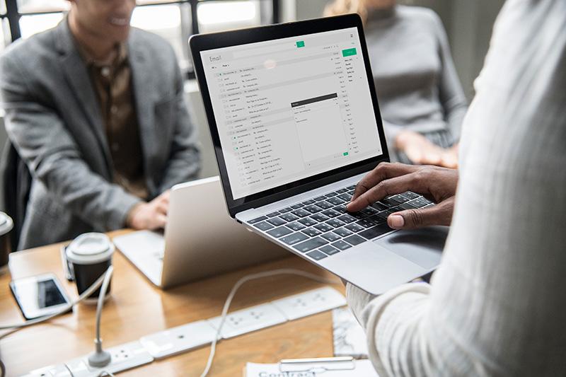Duas pessoas trabalhando em seus computadores, uma em primeiro plano checando seus emails com contratos